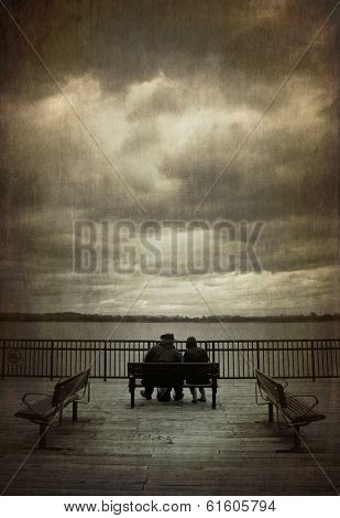 Two friends sit on a bench with a dramatic sky during fall season.   Cross processed to look like an aged instant picture with textures