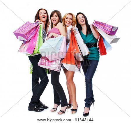 group of four happy young adult women out of shopping with colored bags