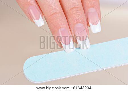 Woman polishing fingernails on hand with nailfile - macro shot, soft focus