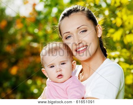 Portrait of beautiful happy mather with baby outdoor, on nature