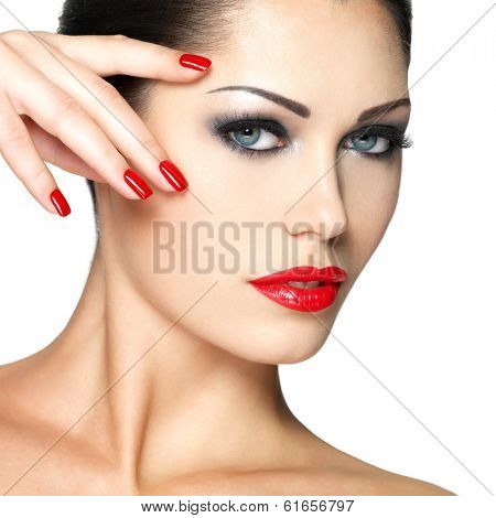 Beautiful young woman with red nails and fashion makeup - isolated on white background