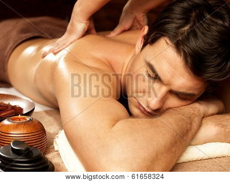 Masseur doing back massage on man body in the spa salon. Beauty treatment concept.