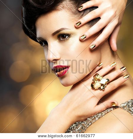 Beautiful fashion woman with golden nails and gold ring over style background