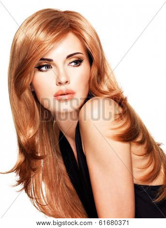 Beautiful woman with long straight red hair in a black dress. Fashion model posing at studio. Isolated on white