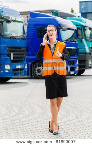 Logistics - female forwarder or supervisor with mobile phone, in front of trucks and trailers, on transshipment point