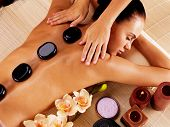 Adult woman having hot stone massage in spa salon. Beauty treatment concept. poster