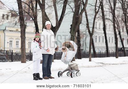 Father And Son Walking With A Baby Stroller In A City Park On A Cold Snow Day