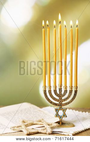 Menorah, star of David and page of Genesis book on wooden table, on bright background