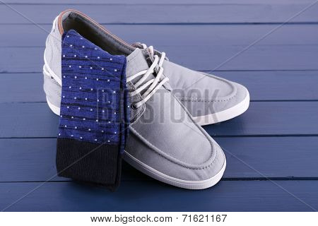 Top-Siders and pair of socks on dark blue wooden background