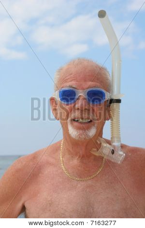 Senior man with dive goggles and snorkel gear on a beach
