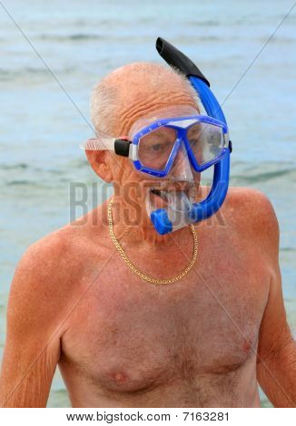 Older man in snorkel and dive mask on a beach