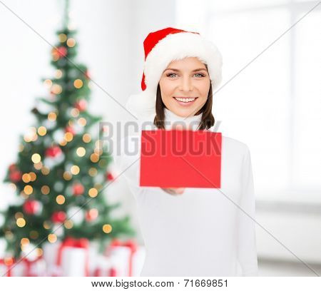 christmas, holdays, people, advertisement and sale concept - happy woman in santa helper hat with blank red card over living room and christmas tree background