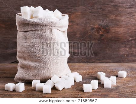 Refined sugar in bag on wooden background