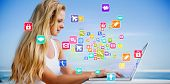 Pretty blonde using her laptop at the beach against colourful computer applications poster
