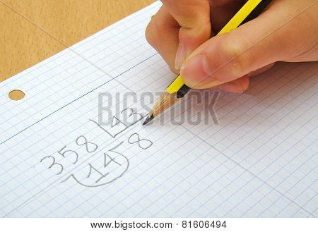 Closeup on the hands of a child doing maths. Division. School concept.