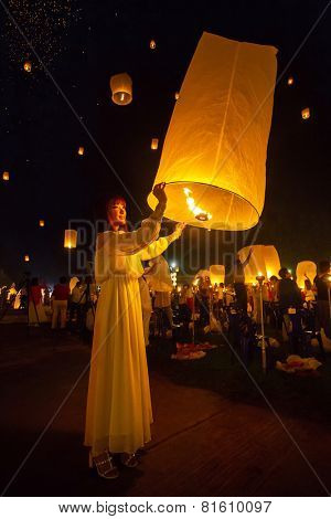 CHIANG MAI, THAILAND - NOVEMBER 8, 2014: Unidentified woman releases Khom Loi, the sky lanterns during Yi Peng or Loi Krathong festival on November 8, 2014 in Mae Jo University, Chiang Mai, Thailand.
