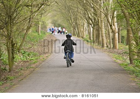A Young Six Year Old Boy Riding His Bke Along A Cycle Trail