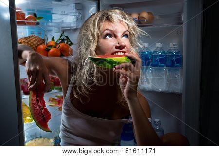 Diet. Beautiful Young Woman near the Refrigerator with healthy food. Fruits in a Fridge