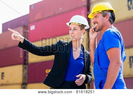 Freight shipping at container terminal of port, worker and manager discussing shipments