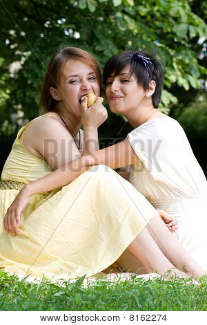 Two Girls Eating An Apple Outdoors Smiling