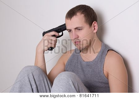Young Man Sitting With Gun Trying To Make Suicide