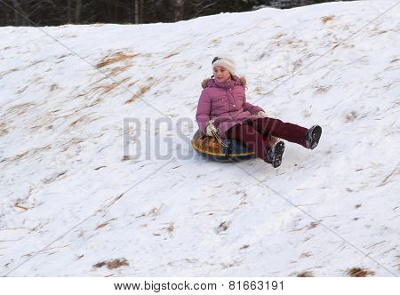 happy teenage girl sliding down on snow tube