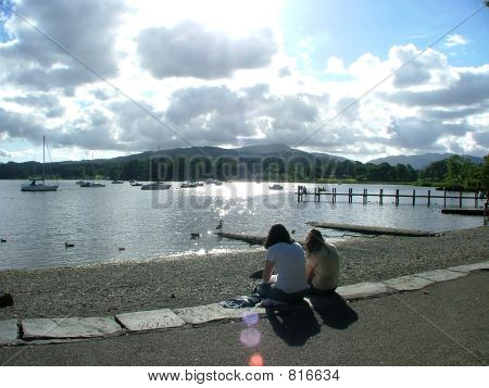 Teo girls sitting by a lake.