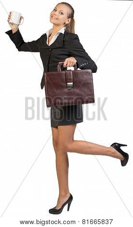 Businesswoman holding mug and briefcase