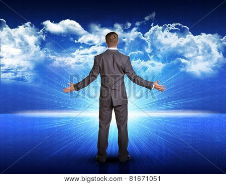 Businessman standing against blue landscape with rising sun