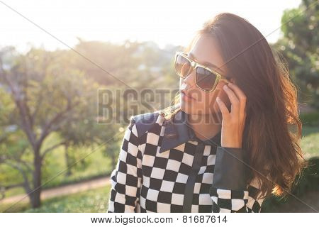 Portrait Of Beautiful Chick Fashion Woman Wearing Sun Glasses Against Afternoon Light With Blur Back