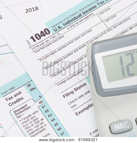 Calculator over US 1040 Tax Form - studio shot poster