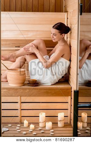 Young woman in white towel resting in Finnish sauna with candles and jar full of water poster
