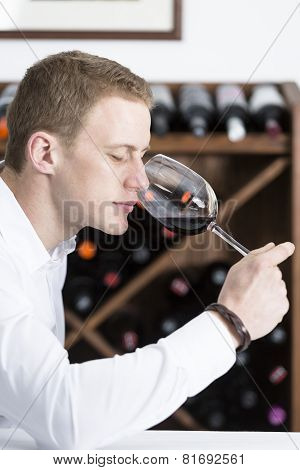 Man Smelling A Glass Of Red Wine.