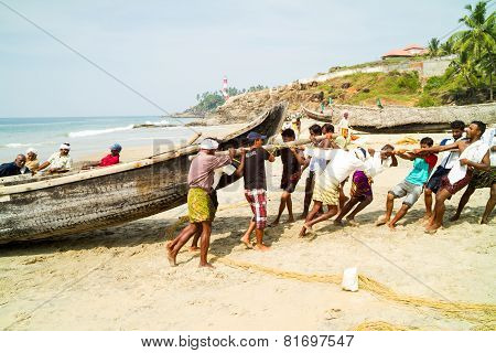 Fishermen Pushing The Fishing Boat On The Beach Out Of The Arabian Sea