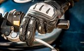 Human hand in a Motorcycle Racing Gloves holds a motorcycle throttle control. Hand protection from falls and accidents. poster