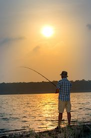 Young Man Fishing From A Shore At Sunset