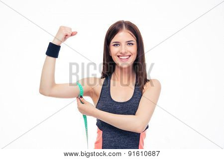 Happy fitness woman measuring her biceps with measurement tape isolated on a white background. Looking at camera