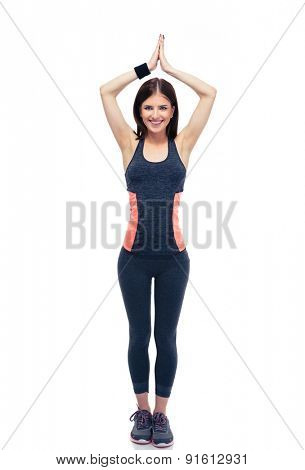 Full length portrait of a happy fitness woman doing yoga excersise isolated on a white background. Looking at camera