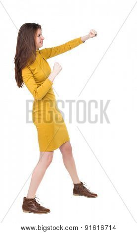 skinny woman funny fights waving his arms and legs. Rear view people collection.  backside view of person.  Girl engineer in the yellow dress standing right side and hit his left hand.