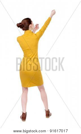 back view of standing girl pulling a rope from the top or cling to something. girl  watching.   Isolated over white background. Girl in mustard strict dress pulling a rope at the top right.