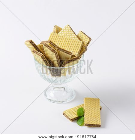 chocolate wafers in glass rummer on white background
