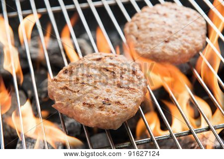 Hamburgers On Grill With Dancing Flames Cooked
