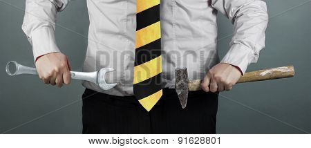 Businessman Holding Hammer And Spanner In Hand And Working Zone Black And Yellow Stripes Cravat