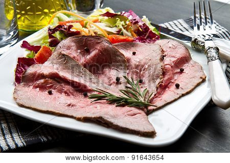 sliced roastbeef with salad on white dish