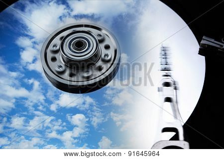 Cloud storage or cloud drive concept image. Hard disk (HDD or Hard drive) with clouds and sky reflecting on disk. Head and Axis with motion blur.