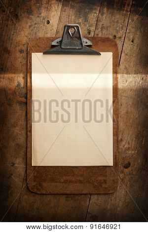 An vintage clipboard on a old wooden desk, with blank paper. intentionally shot with a beam of horizontal light (highlighting) to emphasize your message (to be inserted).