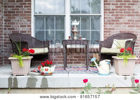 Wicker furniture on the patio with a samovar and tea cups ready for a relaxing tea break in the spring sunshine with pretty flowering potted plants poster