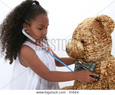 Adorable Little Playing Doctor To A Teddy Bear Over White
