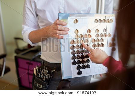 beauty, hair dyeing and people concept - happy young woman with hairdresser choosing hair color from palette samples at salon poster