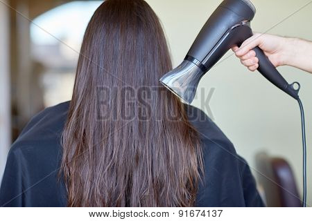 beauty, haircare, blow-dry, hairstyle and people concept - stylist hand with fan dries woman hair at salon